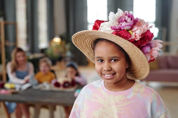 Graziosa bambina di razza mista con cappello decorato con grandi fiori fatti a mano di colori bianco, rosa e cremisi in piedi contro i suoi amici a tavola