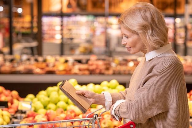 Donna bionda abbastanza matura con il blocco note sopra il carrello che legge la lista della spesa mentre cammina lungo il display con frutta fresca in supermercato