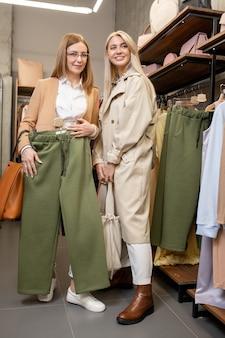 Donna abbastanza matura che prova i nuovi pantaloni verdi davanti allo specchio mentre si consulta con sua figlia nella boutique moderna