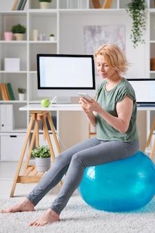 Donna abbastanza matura in activewear che si siede sulla palla fitness e lo scorrimento del corso di formazione online in smartphone a casa
