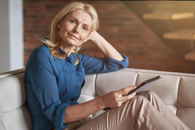 Donna abbastanza matura che guarda la telecamera mentre tiene in mano un tablet pc digitale che si rilassa su un divano a casa