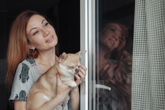 Donna abbastanza matura con il cane chihuahua in mano sul balcone di casa. femmina di mezza età e il suo cagnolino chihuahua. concetto di amore per animali domestici e amico di famiglia