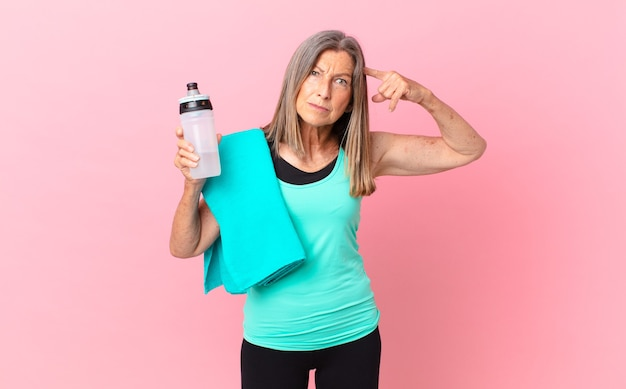 Bella donna di mezza età che si sente confusa e perplessa, mostrando che sei pazzo. concetto di fitness