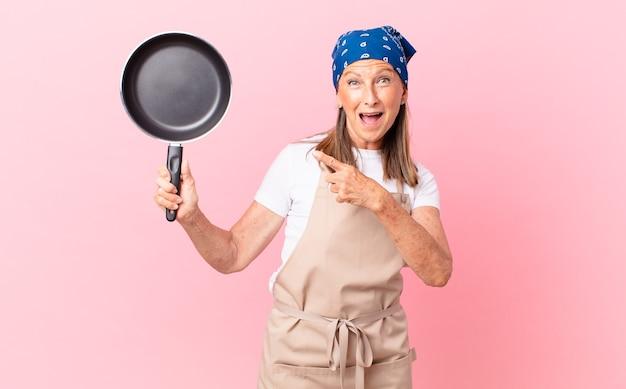 Bella donna di mezza età che sembra eccitata e sorpresa indicando il lato e tenendo una padella. concetto di chef