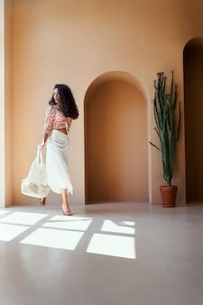 Bella modella in abiti estivi alla moda guardando la finestra