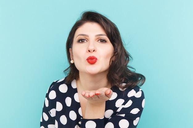 Bella modella con trucco luminoso e labbra rosse che fanno bacio d'aria.