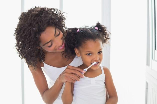 Madre graziosa che aiuta sua figlia a lavarsi i denti
