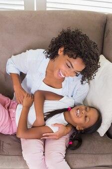 Madre graziosa che si siede sullo strato che solleticava figlia