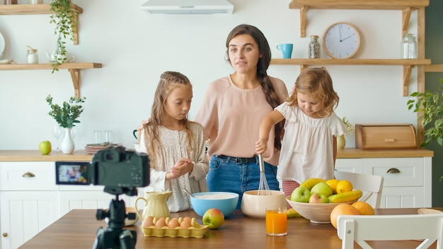 Una bella madre con una figlia carina che riprende un blog sulla cucina. videoblog sul cibo sano. madre e figlia che cucinano insieme sulla fotocamera. madre adorabile che insegna a sua figlia a cucinare