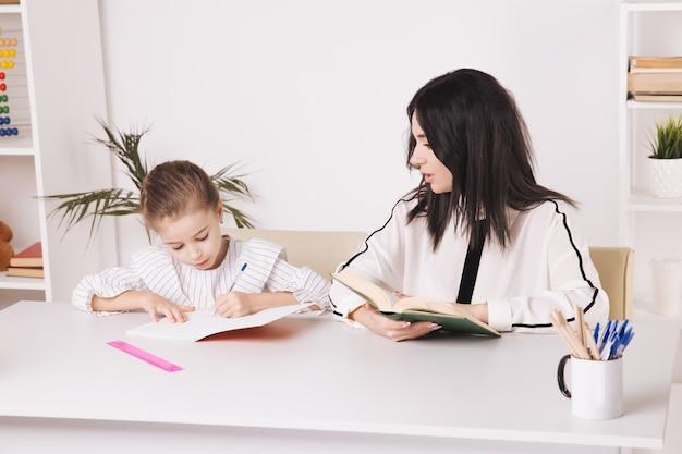 Bella madre con figlia carina seduta con il libro nella stanza di casa.