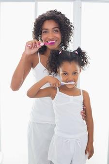 Bella madre con sua figlia lavarsi i denti