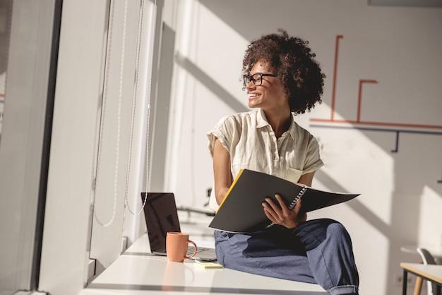 Bella signora multietnica seduta alla scrivania in ufficio