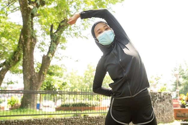 Una bella atleta musulmana che si allunga ed esercita il suo corpo all'aperto e indossa una maschera facciale per proteggersi dai virus