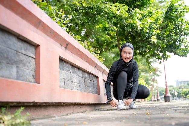 Una bella atleta musulmana che si allaccia le scarpe prima di correre all'aperto
