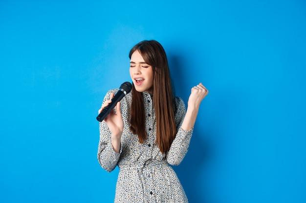 Ragazza abbastanza naturale in vestito che canta canzoni nel microfono, che tiene il microfono e che sembra appassionata durante l'esecuzione, in piedi sul blu.