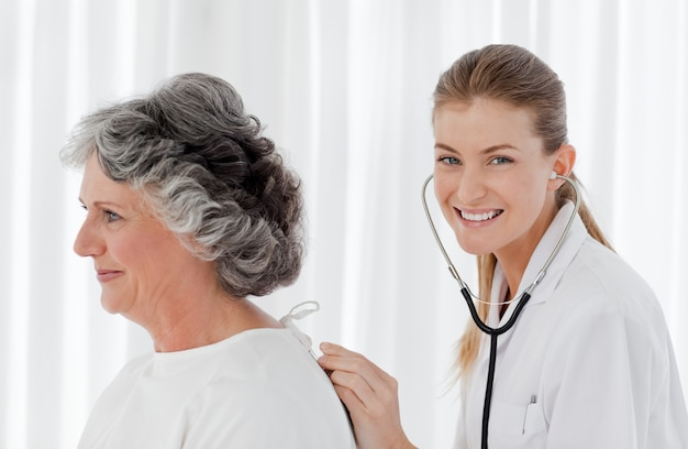 Bella infermiera che prende il battito del cuore del suo paziente