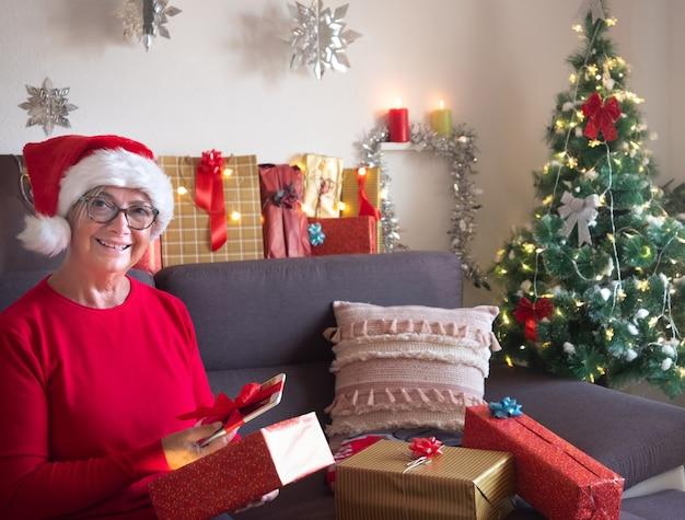 La bella signora anziana con il cappello di babbo natale apre il suo regalo di natale trovando un nuovo tablet. albero di natale e regali per la famiglia che la circonda