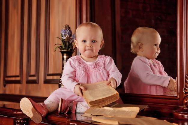 Bella ragazza di un anno in abito rosa con un vecchio libro è seduta sulla credenza vicino allo specchio. bambino nell'interno della biblioteca. concetto di educazione e educazione dei figli. sfondo per sito o banner. copia spazio