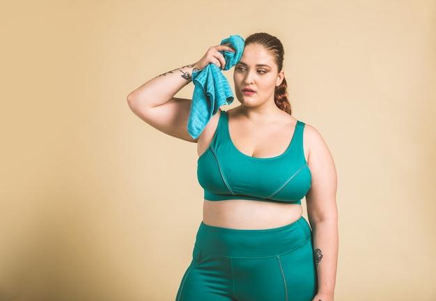 Donna abbastanza oversize che indossa abiti sportivi in posa in studio