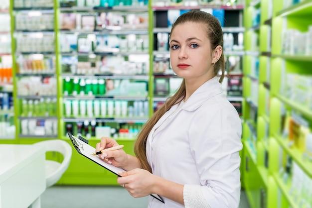 Grazioso farmacista controllando l'elenco dei farmaci in farmacia