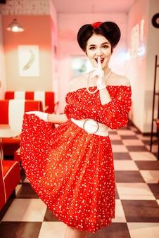Bella donna pin-up con trucco, vestito rosso con pois bianchi, stile vintage. interiore del caffè retrò con pavimento a scacchiera