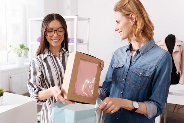Donna abbastanza piacevole che tiene una scatola con un vestito rosa nelle sue mani mentre il suo collega tiene una borsa blu per questo