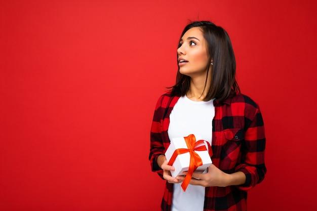 Muro isolato di una giovane donna bruna abbastanza positiva che indossa una maglietta casual bianca