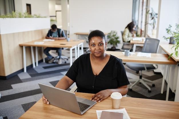 Giovane imprenditrice abbastanza positiva seduta alla scrivania con una tazza di caffè e un computer portatile aperto...