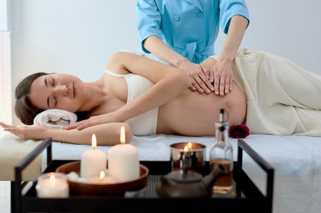Una bella bruna incinta giace su un fianco alla reception con un massaggiatore nella sala di cosmetologia, facendo massaggi sulla pancia, rilassandosi. trattamento termale, concetto di gravidanza