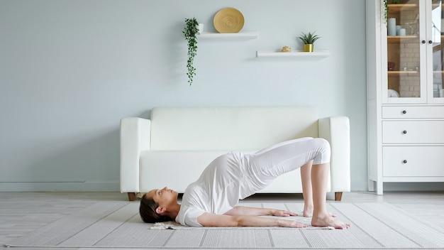 La signora abbastanza incinta fa esercizi praticando lo yoga a casa