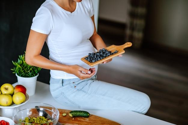 Donna incinta graziosa in camicia bianca e jeans che si siede su un tavolo da cucina e che tiene la compressa con mirtillo.