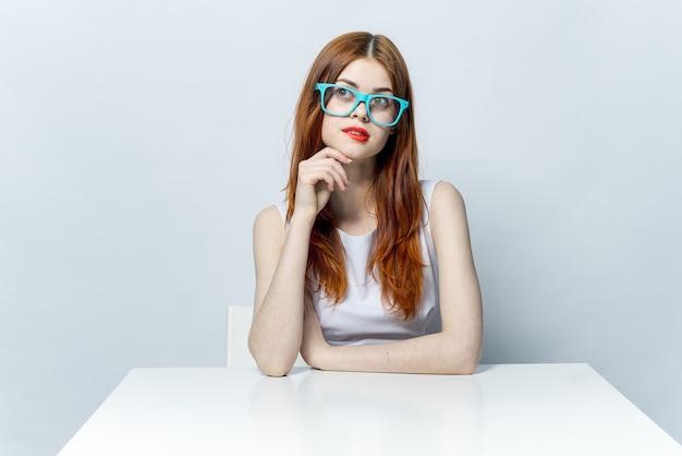 Bella donna dai capelli rossi seduta al tavolo con gli occhiali blu labbra rosse. foto di alta qualità