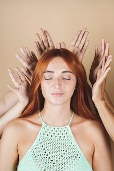 Bella donna dai capelli rossi con le mani sulla testa, con gli occhi chiusi, la moda e la bellezza