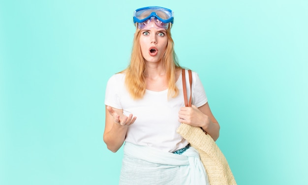Bella donna dai capelli rossi stupita, scioccata e stupita con un'incredibile sorpresa con gli occhiali. concetto di estate