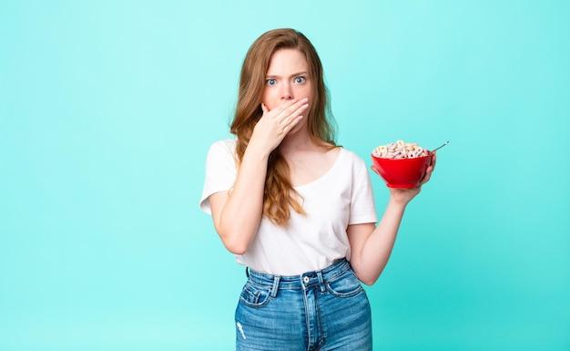 Bella donna dai capelli rossi che copre la bocca con le mani con una scodella scioccata e con in mano una ciotola per la colazione
