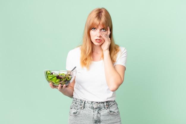Una bella donna dai capelli rossi che si sente annoiata, frustrata e assonnata dopo una noiosa e con in mano un'insalata. concetto di dieta