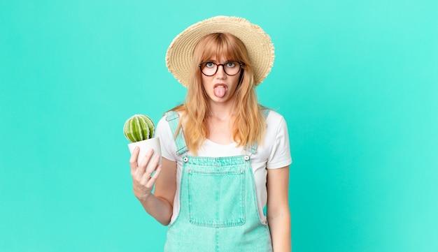 Bella donna dai capelli rossi che si sente disgustata e irritata e fa la lingua fuori e tiene in mano un cactus in vaso. concetto di contadino