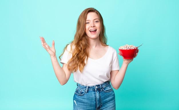 Una bella donna dai capelli rossi che si sente felice, sorpresa di aver realizzato una soluzione o un'idea e con in mano una ciotola per la colazione