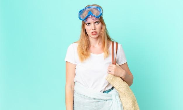 Bella donna dai capelli rossi che si sente perplessa e confusa con gli occhiali. concetto di estate