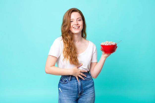 Una bella donna dai capelli rossi che ride ad alta voce per qualche scherzo esilarante e tiene in mano una ciotola per la colazione