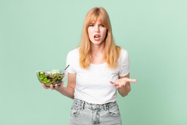 Bella donna dalla testa rossa che sembra arrabbiata, infastidita e frustrata e con in mano un'insalata. concetto di dieta