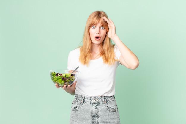 Bella donna dalla testa rossa che sembra felice, stupita e sorpresa e tiene in mano un'insalata. concetto di dieta