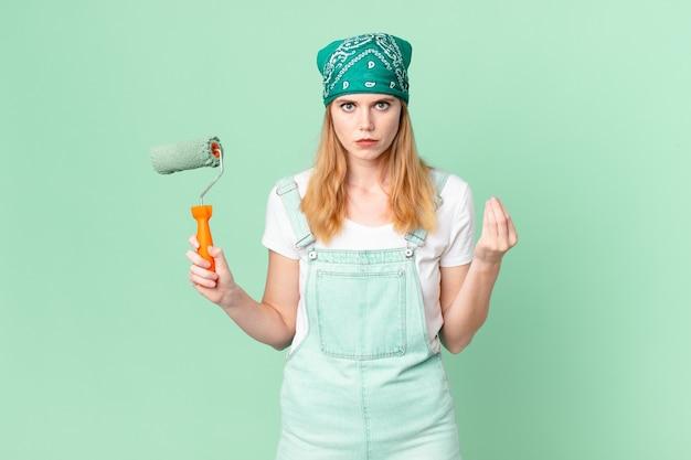Bella donna dalla testa rossa che fa un gesto di capice o denaro, dicendoti di pagare il concetto di casa di pittura