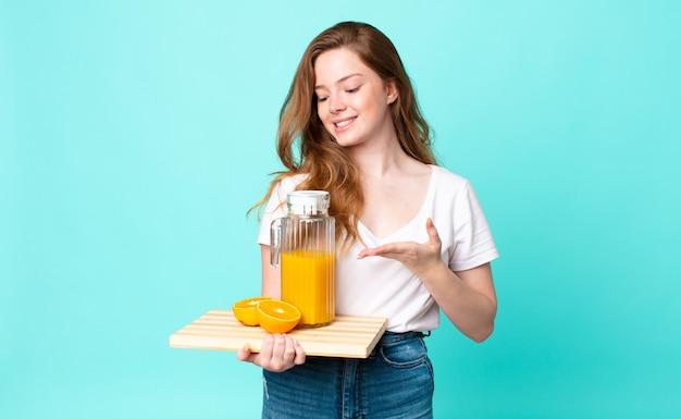 Bella donna dalla testa rossa che sorride allegramente, si sente felice e mostra un concetto e tiene in mano un succo d'arancia