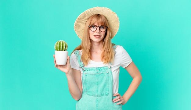 Bella donna dalla testa rossa che sorride felicemente con una mano sull'anca e sicura e tiene in mano un cactus in vaso. concetto di contadino