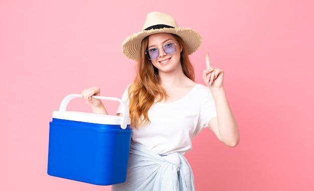 Una bella donna dai capelli rossi che sorride e sembra amichevole, mostra il numero uno e tiene in mano un frigorifero portatile da picnic