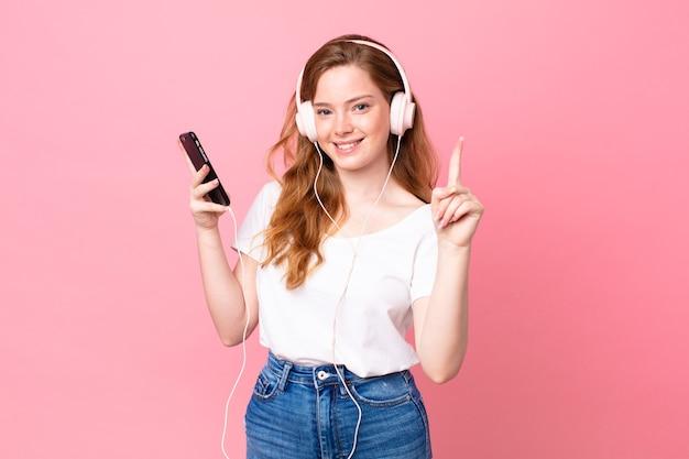 Bella donna dalla testa rossa che sorride e sembra amichevole, mostrando il numero uno con le cuffie e lo smartphone