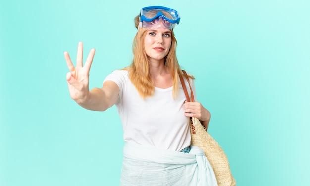 Bella donna dalla testa rossa che sorride e sembra amichevole, mostrando il numero tre con gli occhiali. concetto di estate