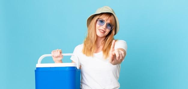 Bella donna con la testa rossa che sorride con orgoglio e sicurezza facendo il numero uno e tenendo in mano un frigorifero portatile. concetto di estate