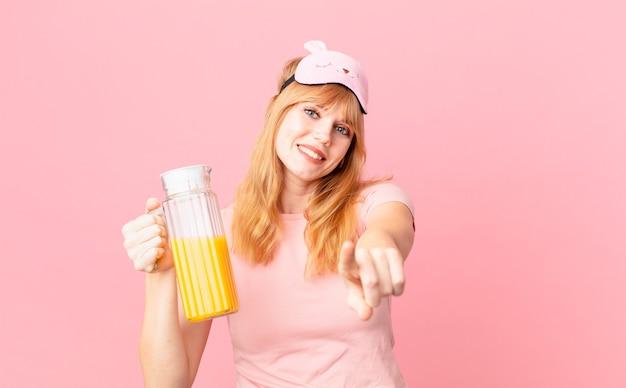 Bella donna dalla testa rossa che indossa un pigiama e tiene in mano un succo d'arancia. concetto di colazione salutare